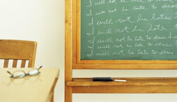 Repeated text written on blackboard in classroom