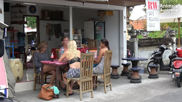 Tourists sit at a Balinese food stall advertising 'RW' for sale. Many tourists don't realise this means...
