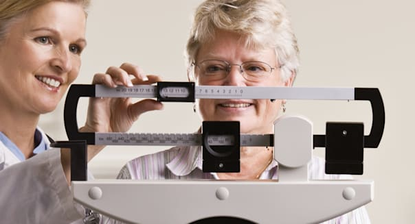 Doctor weighing senior woman in doctor office