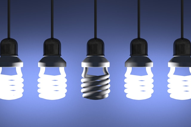 Switched off fluorescent light bulb hanging among glowing ones on blue textured background