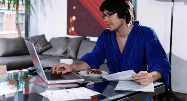 Young man wearing robe, paying bills online