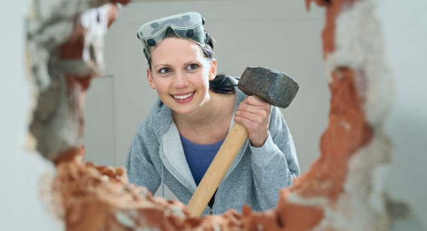 Young woman holding hammer, looking through hole in wall, smiling