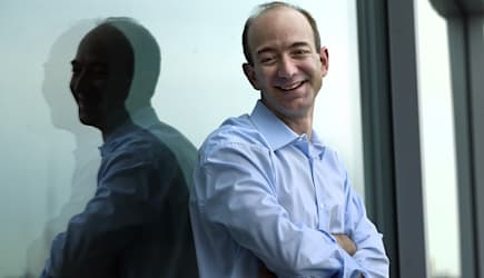 AMAZONS TRIP (Jeff Bezos, founder, CEO and chairman of Amazon.com, stands with one of the company's trademark door-desks at thei