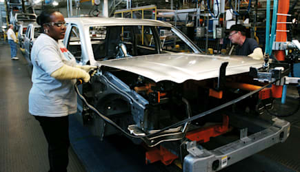 Assembly line technicians secure the hood on a 2005 Jeep Gra