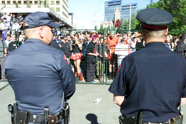 Calgary Police Service officers keep watch over protesters at an anti-World Petroleum Congress in Calgary...