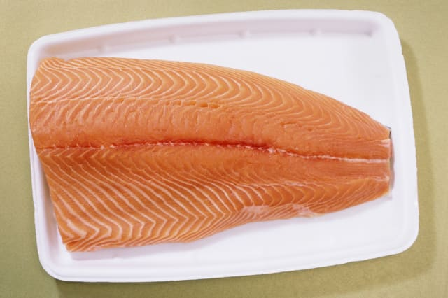 Fresh farmed atlantic salmon on styrofoam supermarket tray