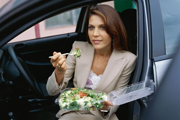 Close up of a young woman sitting in a car and eating salad
