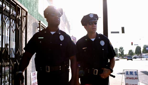 Two policemen wearing sungalsses, walking down sidewalk