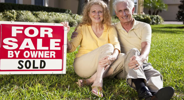 Senior Couple With For Sale Sold By Owner House SIgn