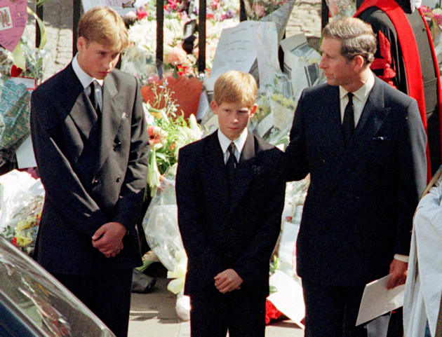 Prince Charles touches the shoulder of his son Harry as his other son Prince William watches the hearse...