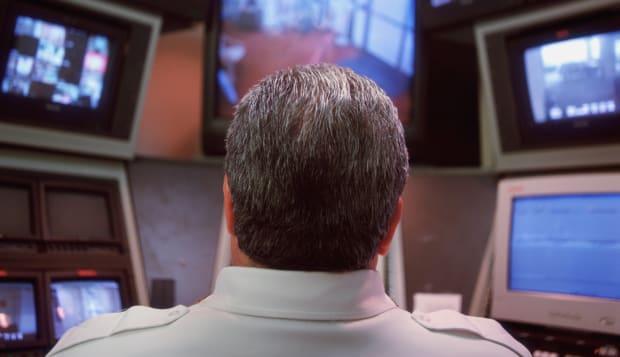 Security guard looking at monitors, rear view
