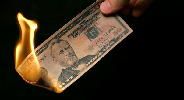 Money To Burn! A hand holding a Fifty Dollar Bill on fire.