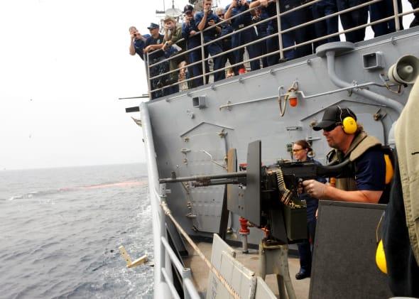 Le chanteur de country Toby Keith tire avec une mitrailleuse à bord du croiseur lance-missiles USS Leyte...