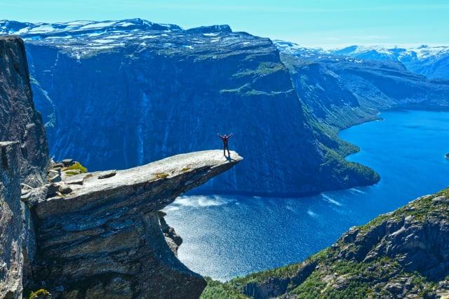 Trolltunga summer view (Norway) and man on rocks edge.