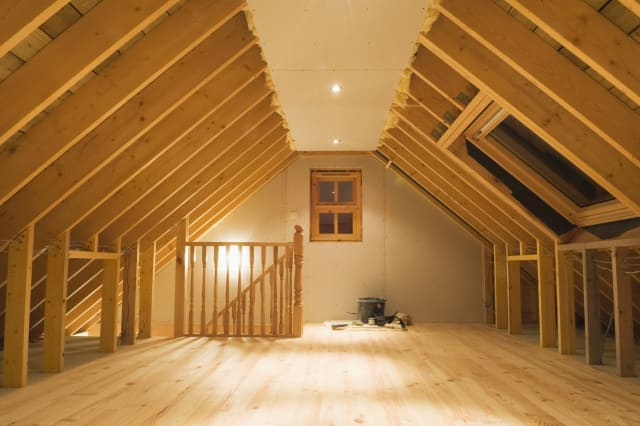 'Nearly finished loft conversion with beams still exposed, and new wooden floor.'