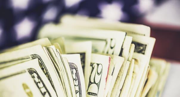 Fan of American twenty dollar bills against US flag