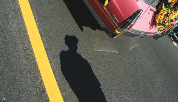Shadow of woman standing by car with wreath attached to trunk
