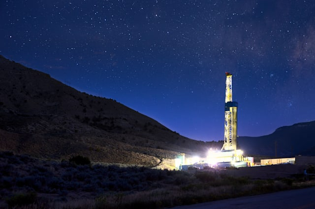 BFracking Rightly lit drilling Fracking Rig in a town at night with star trails above Fracking Oil Well is conducting a fracking