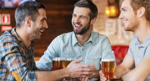 Three happy young men in casual wear talking and drinking beer while sitting in bar together