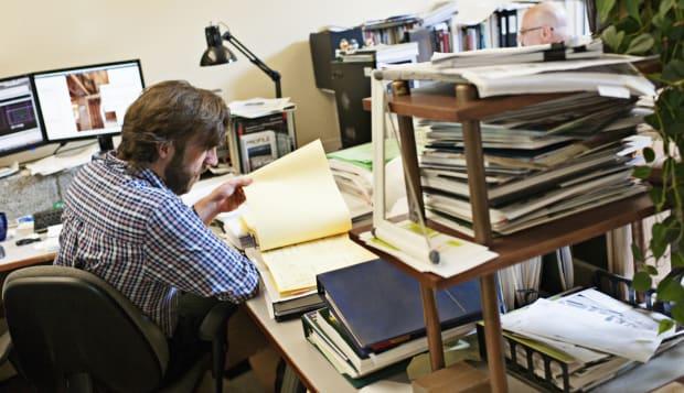 Man checks paperwork at desk