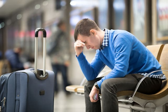 Portrait of young handsome guy wearing casual style clothes waiting for transport. Tired traveler man travelling with suitcase s