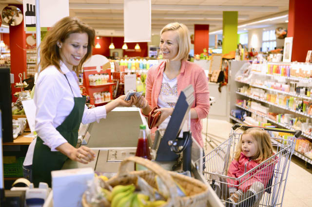Mother and daughter paying at the checkout organic grocery store
