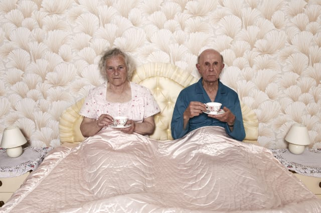 Old couple drinking tea in bed