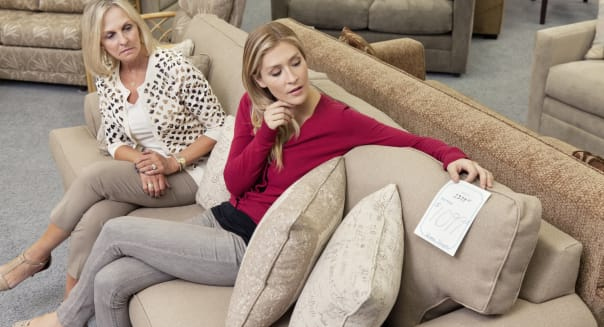 Mother and daughter sitting on sofa while looking at price tag in furniture store
