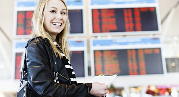 Excited young traveler with boarding pass in airport concourse