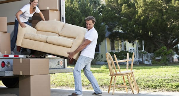 'Couple moving house, loading or unloading couch in moving van'