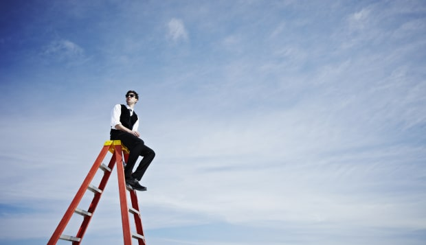 Businessman sitting on top of ladder looking out