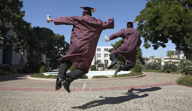 Two male graduate students jumping for joy, outdoors