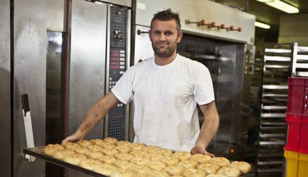 Germany, Bavaria, Munich, Baker holding tray full of bread rolls, portrait