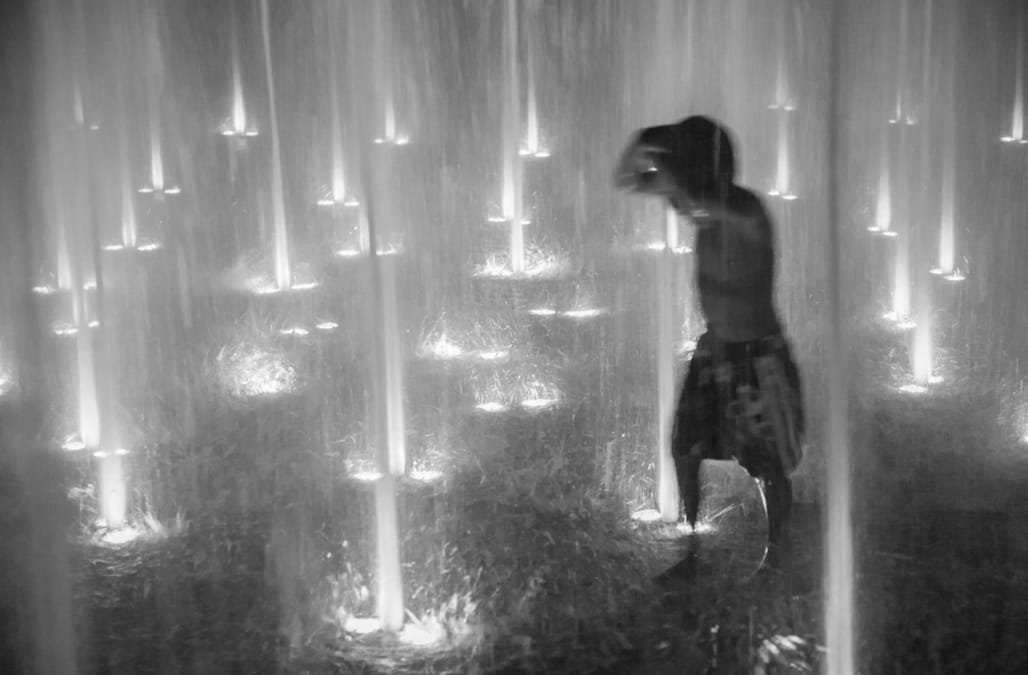 Child Playing in an Illuminated Fountain at Night