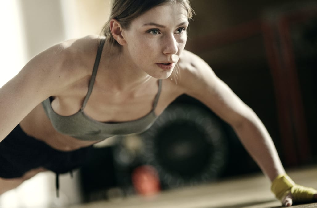Focused female boxer doing push-ups