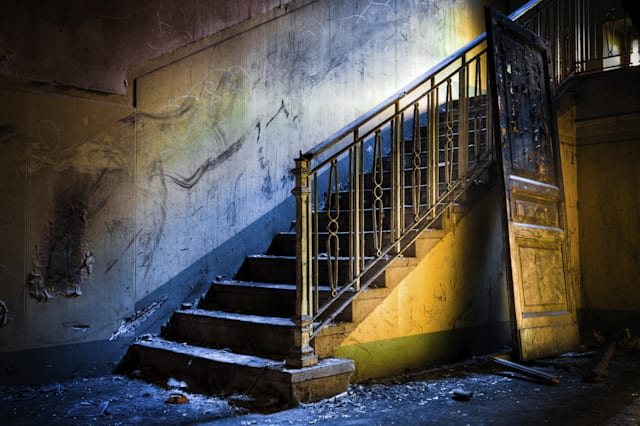 The Ghost House: interior of an abandoned house, very dirty and messy, with rotten walls and staircases.