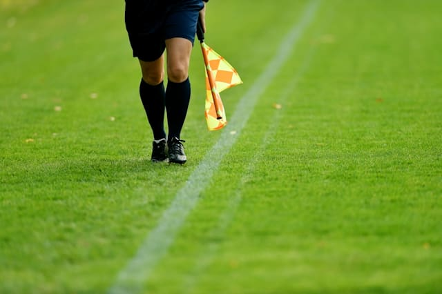 Assistant referee running along the sideline during a soccer match