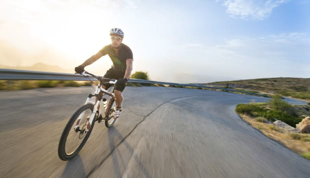 Cyclist man riding mountain bike in sunny day.