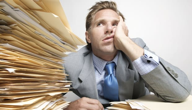 Bored Businessman Looks at Stack of Paperwork