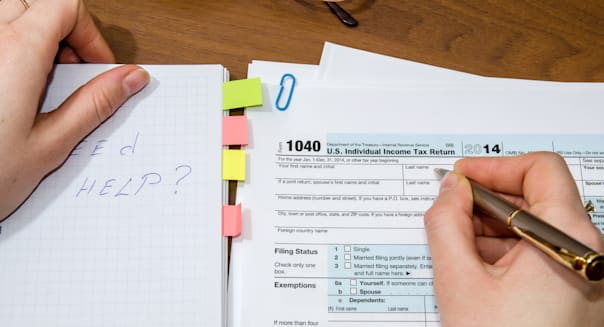 businesswoman hand filling out 1040 tax form