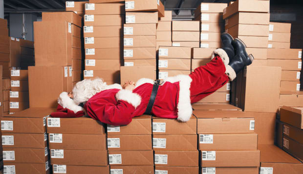 Santa lying on boxes in storage room, side view