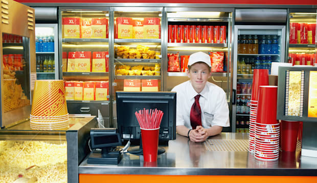 Teenage boy (14-16) serving at popcorn counter, smilng, portrait