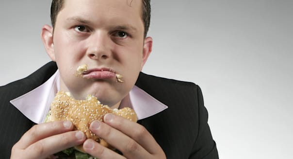 disappointed businessman eating ...