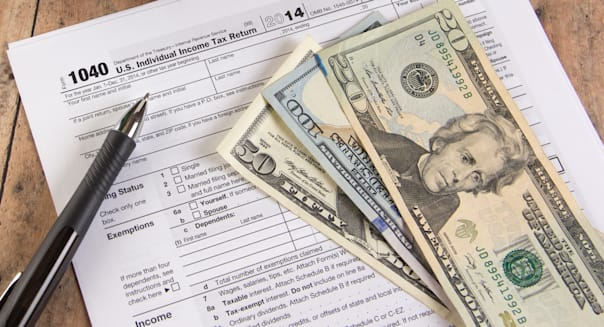 Income tax form 1040 with calculator and dollar bills