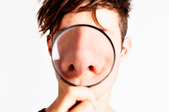 Cute but nerdy young man holds up a magnifying glass, enlarging his nose enormously - all the better to smell you with!