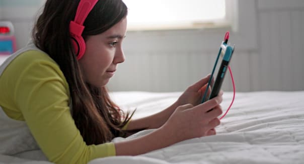 Child with headphones and playing with tablet