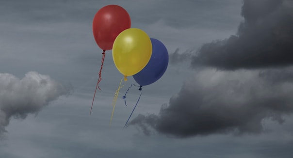 Balloons floating through dark sky