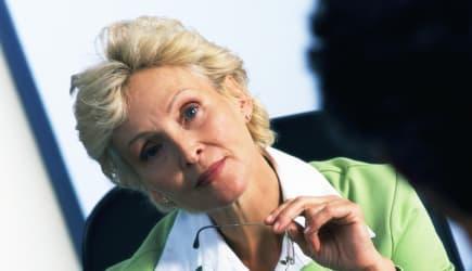 Businesswoman sitting in armchair, blurred foreground