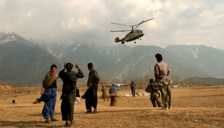 APTOPIX PAKISTAN SOUTH ASIA EARTHQUAKE (People watch a helicopter from the World Food Program arrive at the village of Paca Biak