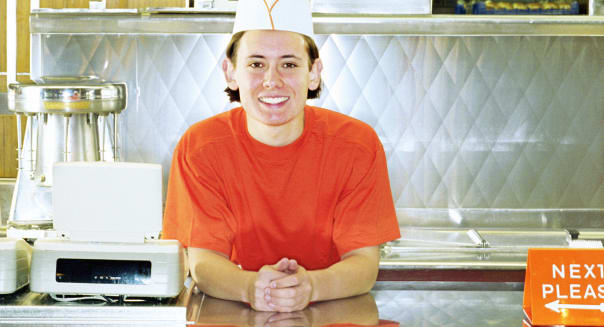 Teenage boy (17-19) working behind counter of fast-food restaurant